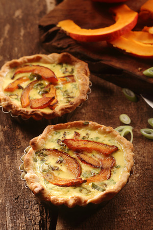 pastry crust: Tasty homemade butternut quiche or flans with a crispy pastry crust and slices of squash in a custard and herb base on a rustic wooden table
