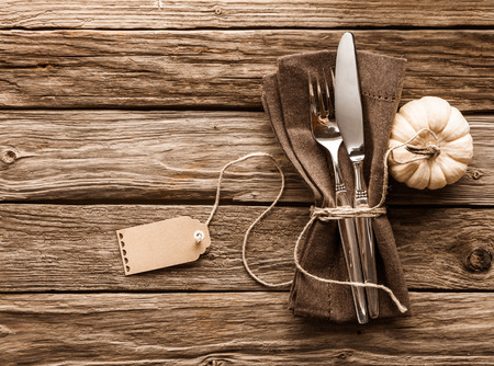string together: Autumn or fall table setting with an ornamental white gourd alongside a knife and fork tied together with a brown napkin with string and a blank gift tag on a rustic wooden table