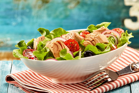 Delicious tuna fish salad with green leaf lettuce, tomato and onions in bowl with fork and napking over wooden table