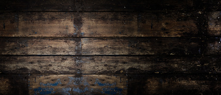 building materials: Old weathered wooden panoramic banner background with a vignette and off center highlight with copy space and texture for your text