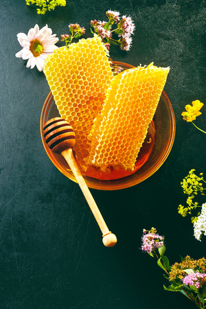 Delicious fresh honeycomb with scattered wildflowers and a wooden honey dipper in a shallow bowl viewed from above on slate with copy space