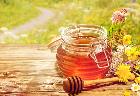 tipped: Large glass jar of honey with wooden round tipped dipper on table in field of wildflowers outdoors Stock Photo