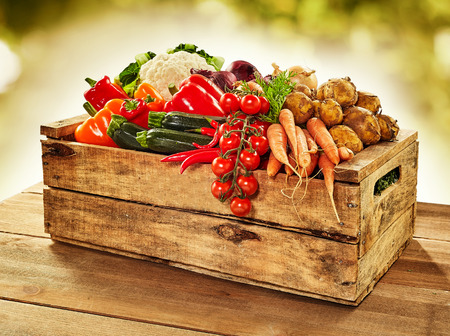 Wooden crate filled with farm fresh vegetables including onions, tomato, peppers, potato, carrots , courgettes and cauliflower, on a wooden table outdoors at market Stockfoto