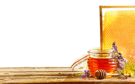 tipped: Single beehive shaped container of honey and wooden round tipped dipper behind large frame of honeycomb on table. Includes white space.