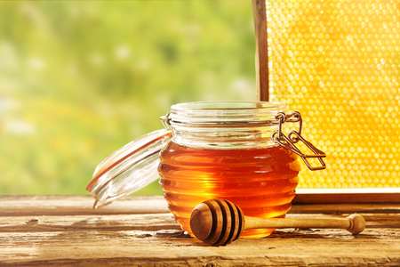 tipped: Honeycomb behind large glass resealable jar of honey with wooden round tipped dipper on table Stock Photo