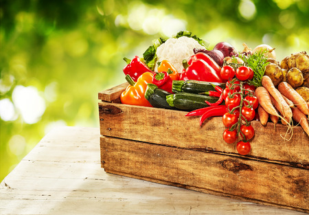 produces: Farm fresh vegetables in a wooden crate with tomatoes, courgettes, carrots, cauliflower and sweet peppers on an outdoor rustic table at market