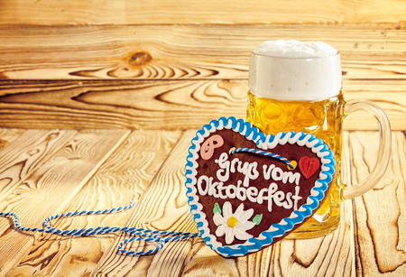 gingerbread heart: Speciality gingerbread heart to celebrate the Oktoberfest decorated with a German greeting in icing propped against a mug of golden frothy beer on a wooden background with copy space