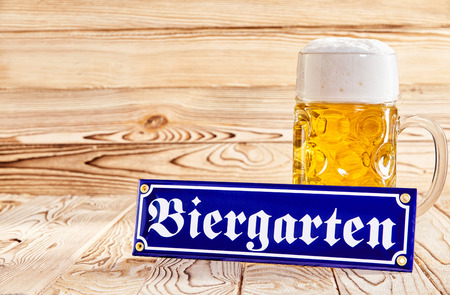 Oktoberfest Biergarten, or Beer Garden, concept with a blue German text sign propped against a glass mug of golden frothy beer on a wooden background with copy space Standard-Bild