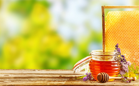 Jar of fresh honey with assorted wildflowers, a wooden dispenser and tray of honeycomb from a bee hive in a still life on a wooden table outdoors with copy space
