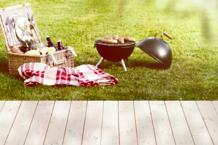 Open picnic basket near a folded red checkered tablecloth and a round barbecue grill on the green lawn