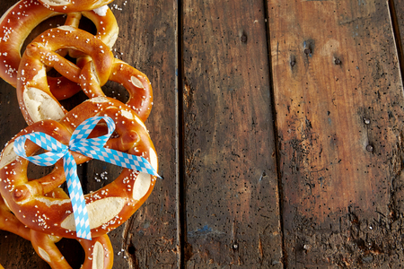 Tasty salted Bavarian pretzel biscuits forming a side border on old aged dark wood with copy space for Oktoberfest themes
