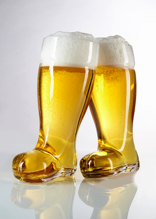 novelty: Novelty boot shaped beer glasses filled with frothy golden beer or lager in an Oktoberfest theme on a reflective white background Stock Photo