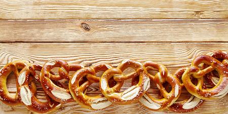madera rústica: frontera de gran angular de pretzels bávaros en un fondo de madera rústica, con copia espacio para los conceptos temáticos Oktoberfest