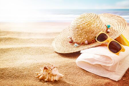 sunhat: Trendy yellow sunglasses, straw sunhat and towel on a beach with a seashell in the foreground and ocean backdrop with sun flare on a summer vacation Stock Photo