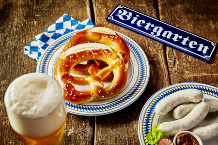 Food and beverage in a beer garden at Oktoberfest with a frothy beer alongside pretzels and a plate of veal sausages in a Bavarian tavern Standard-Bild