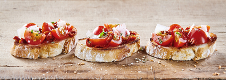 tomato slices: Tomato bruschetta with parmesan cheese served on toasted slices of baguette for a traditional Italian appetizer, panoramic banner format