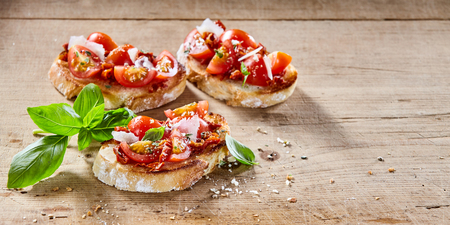 tomato slices: Tasty tomato Italian bruschetta on toasted slices of baguette seasoned with spice and herbs and garnished with fresh basil on a wooden board with copy space, wide angle view Stock Photo