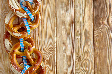 Border of traditional Bavarian pretzels with bows in the colors of the Bavarian flag on a rustic wood background with copy space for Oktoberfest