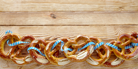 Border of delicious salted Bavarian pretzels tied with ribbon in the Bavarian colors on a rustic wooden background with copy space in wide angle format for the Munich Oktoberfest