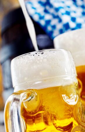biergarten: Cold golden frothy lager being poured into a glass mug with a Bavarian flag in the background conceptual of the Munich Oktoberfest celebration