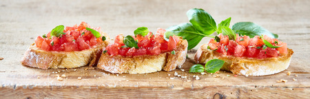 tomato slices: Delicious seasoned savory Italian tomato bruschetta slices on a rustic wooden board garnished with fresh basil leaves, horizontal banner Stock Photo
