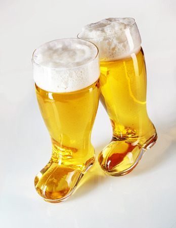 gar: Fun boot shaped beer glasses filled with frothy golden lager on a white background conceptual of the Munich Oktoberfest
