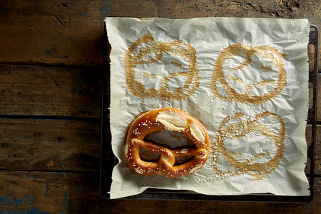 imprints: Overhead view of a square of used oven paper with pretzel imprints and a single remaining biscuit fresh from the oven, on a rustic wood background with copy space