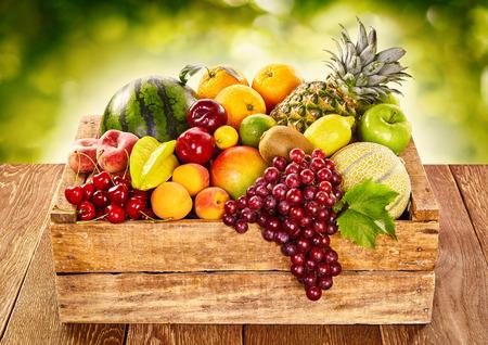 Houten boerenkratje gevuld met vers tropisch fruit op een buitentafel op de markt, inclusief bananen, watermeloen, druiven, sinaasappel, citroen, kiwi, perziken, abrikoos, kers, ananas, meloen en appels Stockfoto