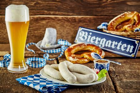 Tavern Mahlzeit für das Münchner Oktoberfest mit traditionellen Weißwürste und Brezeln mit einem eiskalten schaumige Bier in einem langen Glas auf einem rustikalen Theke serviert