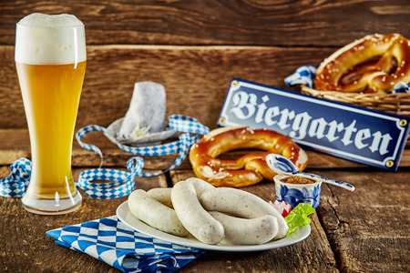 weisswurst: Tavern meal for the Munich Oktoberfest with traditional veal sausages and pretzels served with an ice cold frothy beer in a long glass on a rustic counter