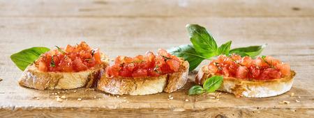 おいしいイタリアのブルスケッタ トマトをトッピング トーストした香ばしいパンと素朴な木の板にバジル添えハーブのパノラマのバナー