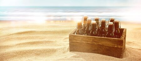 Crate of beers in brown glass bottles with cork on a sunny tropical beach close to the ocean on a hot summer day with copy space