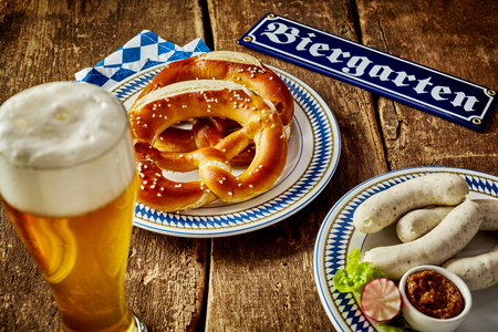 veal sausage: Traditional Bavarian cuisine for Oktoberfest with salted pretzels on a plate alongside a frothy beer and serving of veal sausages with sauce