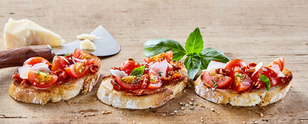 speciality: Speciality Italian bruschetta with parmigiana cheese and tomato topping seasoned with herbs and spices and served on a rustic wooden board Stock Photo