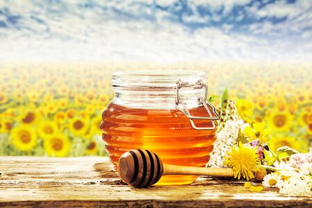 Field of sunflowers behind beehive shaped honey jar, wildflowers and wooden stirrer on table for theme about natural sweetener
