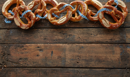 gar: Border of traditional German pretzels on dark aged wood background with copy space for your Oktoberfest themed text