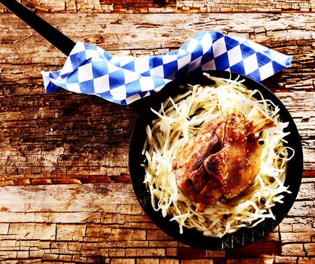 hock: Traditional Bavarian food with grilled ham hock served in a rustic pan on cabbage or sauerkraut, overhead view for an Oktoberfest theme