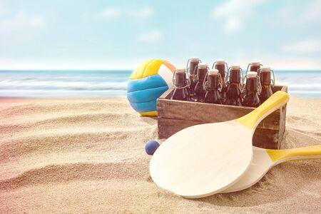 pelota de voley: Caja de cervezas con dos palos de madera y una pelota de volea colorido en una playa junto al mar conceptual de las vacaciones de verano