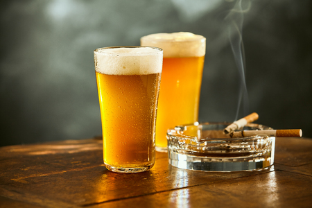 Two chilled beers in long pint glasses with burning cigarettes on an ashtray resting on an old wood counter in a pub or bar in a concept of relaxation and entertaining