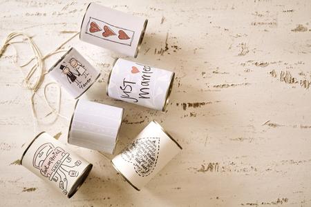 Diverse blikjes met getrouwde etiketten met kopie ruimte over gekraste verf witte achtergrond Stockfoto
