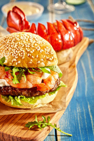 Close up on sesame seed bun shrimp and lettuce hamburger with lobster tail on cutting board over blue table