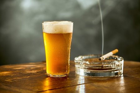 wafting: Chilled glass of beer with a burning cigarette on an ashtray with wafting smoke on a wooden counter in a pub or tavern Stock Photo