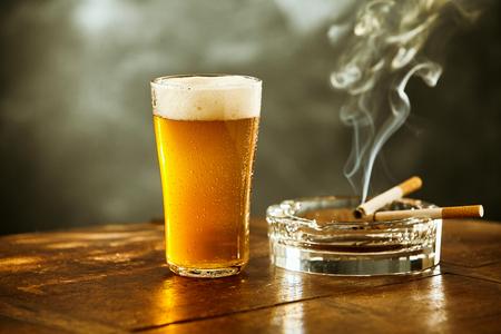 Schuimig ijskoud bier in een groot glas en twee brandende sigaretten die op een asbak in een kroeg rusten, die in een relaxte en verslavingskoncept wafting rookt Stockfoto