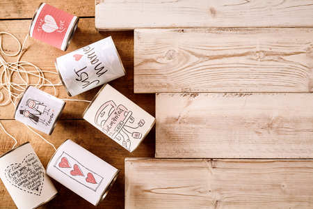 top down car: Cans with various cute just married, hearts, love and wedding symbols over wood plank background