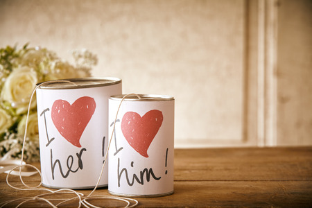I love her and him cans with string in front of bouquet of flowers on table. Includes copy space.