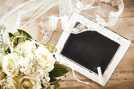 wedding accessories: High Angle Still Life of Blank Chalkboard with Piece of Chalk on Rustic Wooden Table with White Rose Bridal Bouquet and Delicate Lace Veil in Wedding Day Concept Image with Copy Space Stock Photo