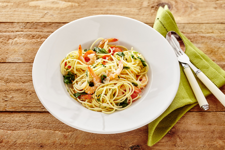 semolina pasta: Tasty gourmet Italian spaghetti or capellini seafood appetizer with prawn tails, tomato and basil for a healthy Mediterranean diet