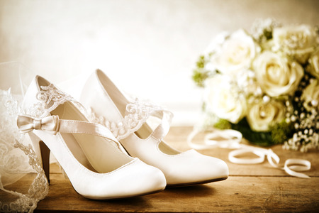 Close Up of Pair of White Satin Bridal Shoes with Straps and Bows on Rustic Wooden Floor or Table with White Rose Bouquet and Lace Veil in Wedding Day Still Life