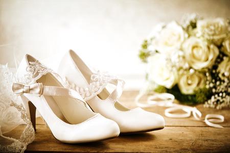Close Up van paar witte satijnen bruids schoenen met riemen en strikken op rustieke houten vloer of tabel met witte roos boeket en Lace sluier in bruiloft dag stilleven