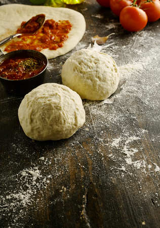 pizza base: Freshly prepared mounds of pizza dough on a wooden counter in a rustic kitchen with a rolled base being spread with fresh tomato paste behind and copy space in the foreground Stock Photo